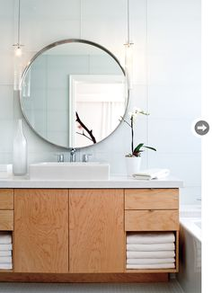Beautiful White Glass Subway tile, round mirror, wooden vanity
