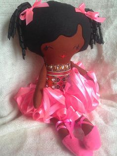 Angelina ballerina black rag doll with body in African print Angelina/Dashiki and coloured tutu. Height of doll 19/49 cms. Limbs and face made from cotton with felt and coiled ribbon hair. Available with orange or pink tutus. This doll can be gently hand washed and the tutu and ballet shoes are removable. Comes in an organza gift bag. Doll stuffed with toy safe inflammable filling BS5852-2.