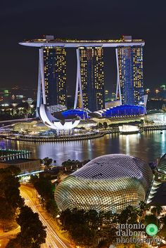Aerial view of Marina Bay at night. In foregraound The Esplanade theatre while in the background the tall towers of Marina Bay Sands.
