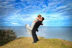 groom lifts bride at the edge of the Charleston Harbor at Sunrise Park