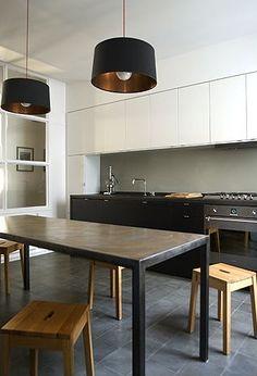 Piękna realizacja. Grafitowa podłoga ze średniej wielkości płytek, stół z ciemnego metalu, drewniane taborety z drewna bukowego i biało czarne rzędy szafek - piękne.