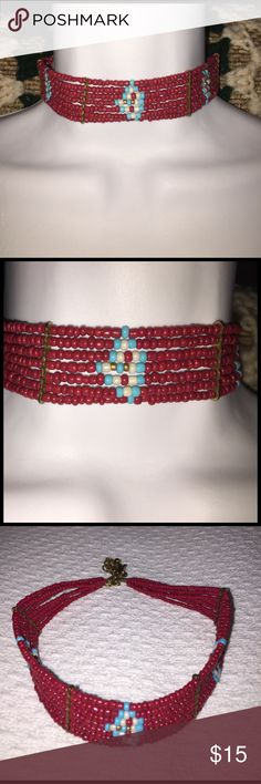 """Native American Tribal Seed Bead Choker Necklace Multi-Strand Native American Tribal Seed Bead Choker Necklace. Features 7 Hand strung strands of cinnamon red seed beads with a triangle design showcasing white, aqua, & gold seed beads. Also has gold tone metal spacer bars. Lobster claw clasp with a 3 1/2"""" extender for a adjustable fit. Measures: 16"""" in total length & 1"""" Wide. Great condition! Jewelry Necklaces"""