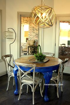 An old carved table with blue painted highlights combines with new reproduction chairs