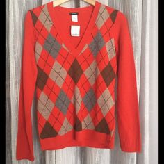Listing!  NWT J Crew Orange Argyle Wool Sweater J Crew orange argyle wool and cashmere sweater. Approximately 24 inches total length, 17 inches armpit to armpit, 18 inches armpit to end of sleeve. Material 90% wool, 10% cashmere J. Crew Sweaters V-Necks