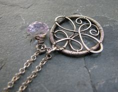 "A single, sparkling Pink Amethyst onion briolette is wire wrapped in Sterling and dangles freely along with it's hand formed ornate charm. A petite 1"" circle coiled with Sterling Silver wire and adorned with an intricate pattern of hammered wire. MEMBER -  Blue Scarab Jewelry"