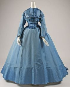 Victorian Dress - lovely blue gown with full skirt, tightly cinched waist.  The bodice is yoked, pleated and trimmed with tassels. High neck; no collar; long sleeves; the bodice and forearms have buttons with frog closures.
