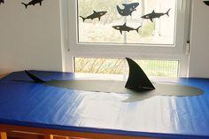 blaues papier als tischdecke, hai draufmalen und flosse anbringen :)