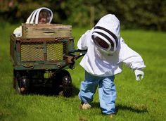 just too sweet - two little kids in bee keeping suits pulling a wagon with a hive.