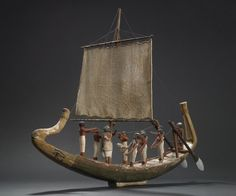 Wooden model of boat with crew: The hull is narrow in proportion to length; ends in a curved finial forward and a straight finial aft, with a short plinth to act as stand. The form of the hull is that of a funeral barge, but the ornamental finials are wrongly placed. This was done anciently, as the painted-plaster coating shows.       12th Dynasty