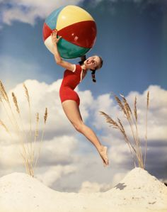 Stock Photo : Happy retro woman jumping holding colorful beach ball