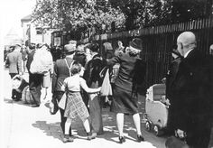 Amsterdam, The Netherlands, People with baggage and a baby carriage on their way to Westerbork, 1943.