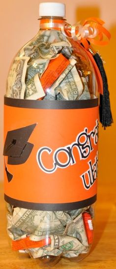 Grad Gift Ideas - carefully cut an opening in the back of an empty 2-liter soda bottle, insert candy and money, then close and cover with scrapbook paper in the graduate's school colors.