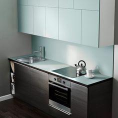 Moderne, kompakt IKEA køkken med lyseblå bordplade og en kombination af skabsfronter af mørkt træ og lyseblå skabsfronter