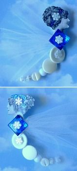 "Winter ""Button Fairy"" ~ ""I used public domain images and edited them in a graphics program. I printed the images in black & white on heavy cardstock and embellished them with blue glitter glue. I coated the images with several layers of clear polyurethane, and added iridescent snowflakes. I threaded white buttons and beads onto white chenille stems, bending hanging loops at the top. I then glued the heads to the top of the button bodies, and added white tulle netting for wings."""