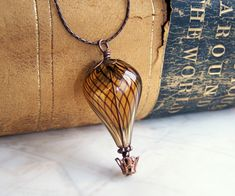 Hot Air Balloon Necklace - A Steampunk balloon in amber blown glass and copper…