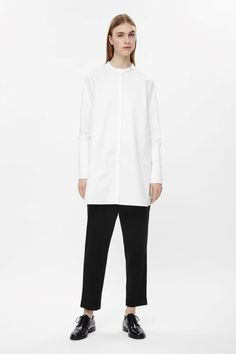 This elongated, tunic-style shirt is made from cotton poplin with wide cuffs that can be left long or folded back. Flaring slightly towards the hem, it has a hidden front button fastening and a single back pleat for volume.