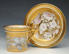 A DERBY GOLD GROUND CABINET CUP AND SAUCER, circa 1820, applied with find white beads or pearls, gilded eagle handle, painted with white and puce flowers reserved against a solid gold ground, the interior of the cup with gold scrollwork border, crown, crossed batons and D mark painted in red, painter's number 37 on both pieces