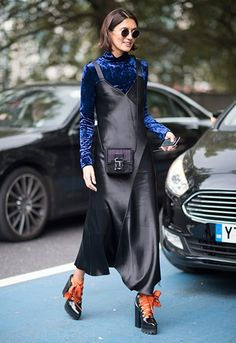 Street style model wearing velvet roll neck layered underneath a black satin slip dress with lace up heels at London Fashion Week