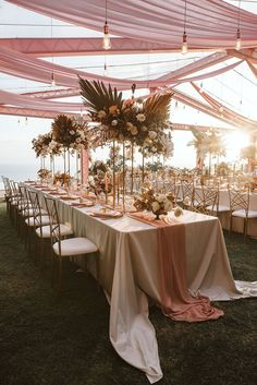 Modern metallics, abstract paper goods, romantic draping and Edison bulb lights? This Phuket destination wedding is a fairytale true and true! Suki and Sing said I Do overlooking a tranquil, sun-kissed sea, followed by an al fresco reception with layered pinks and tall centerpieces. They even shared a first dance surrounded by fountain fireworks to boot! See this romantic Thailand wedding on Ruffled now. #weddinglights #thailandweddingvenue #dyedflowers #orchidbouquet