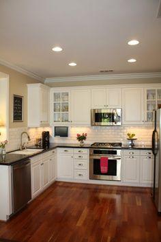 Subway tile, ceiling lights, hardwood floors, dark countertop, light cabinets, large double sink.