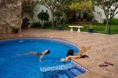 """The photographer's daughters, Sura and Yara, swim in a pool at a friend's home in Dhahran, Saudi Arabia, April 2016. """"They lay there, free, and careless,"""" Alsultan says. """"There's no public pools for women, neither is there any beach spaces for women only. Only privately owned or very expensive clubs that is not available to Saudis."""""""