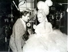 BACKSTAGE: Norma Shearer behind scenes of Marie Antoinette at MGM studios with her costar, Tyrone Power, Count Axel Fersen (who is not in costume here) MGM, 1938. The women's costumes were designed by Gilbert ADRIAN and the men's wardrobe was designed by Gile Steele.