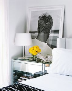 Modern bedroom with gray walls, a mirrored accent table, and large framed black and white photography