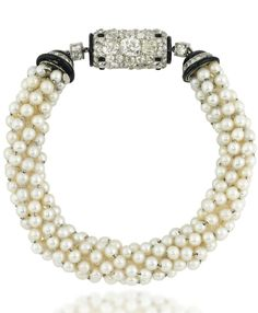 AN ART DECO PEARL, ENAMEL AND DIAMOND BRACELET/WATCH. Designed as a pearl torsade bracelet with black enamel and diamond-set hemispherical terminals, to a pavé-set old-cut diamond rectangular bombé panel centre, with buff top onyx spot detail, the reverse with inset watch, the cream dial with black painted Arabic numerals and blued steel hands, to a polished case, mechanical movement, circa 1920, French marks for platinum, 20.9cm long. Dial signed Cartier, movement unsigned and numbered.