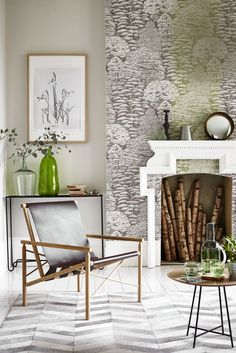 Introduce Greenery into a room with soft furnishings such as vases > Use the same wallpaper in two colours to create an unusual feature wall. Contemporary furniture complements the woodland pattern. For more living room ideas visit housebeautiful.co.uk