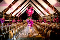 Modern sculpture in rose & fuchsia over a rose gold room adorned with gold mercury candles, gold chairs topped with cascading floral arrangements of violet, fuchsia and hot pink using orchids, wine dahlias, creamy garden roses and delicate lilies. Design by Waterlily Pond / Floral Artistry & Event Design / San Francisco, California. Santa Lucia Preserve, Carmel Valley. Photos courtesy of Larissa Clevelend Photography.