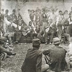 This rare photograph shows a Union army camp scene where soldiers are entertained by a group of African American minstrel performers.