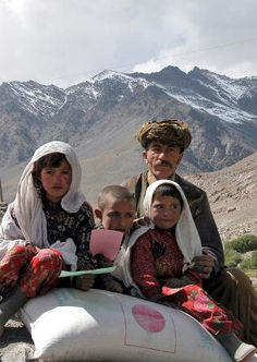 A family in the Wakhan district of Badakhshan Province, Afghanistan, sit on bags of wheat distributed by the United Nations World Food Programme (WFP).  27/11/2007. Wakhan, Afghanistan. UN Photo/WFP.