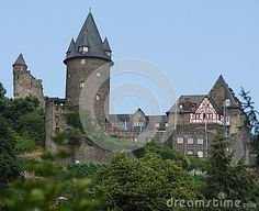 Photo taken in a center called Bacharach along the Rhine valley in Germany. In the image you see on the side of a castle, in particular it left the high circular tower from the tip cone delineated by blue sky. To the right you see the facade of a typical house of the place with wooden logs in the wall.