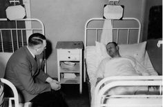 Hitler (with cotton in his ears) visiting a victim of the July 20, 1944 bomb plot.