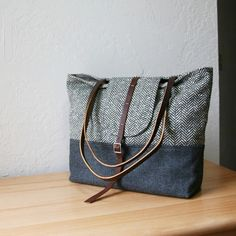 """The upper fabric is a gorgeous vintage herringbone wool in dark olive brown and cream. Base = charcoal gray vintage wool. Lined with gray cotton canvas, and interlined with canvas for additional structure. The straps and adjustable fastener are military surplus genuine leather.    Inside the bag is a large zippered pocket, a slip pocket, a pen slip and a clip for your keys.    Dimensions: 12"""" wide at the base x 11"""" tall x 4"""" deep  Strap Length: 23"""""""