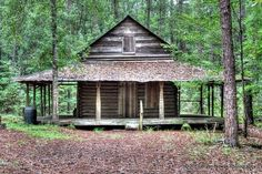 Old log cabin in the woods.  Look at that wrap-around porch.