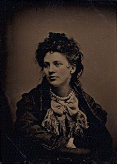 Her eyes instantly give away the fact that this lovely Victorian woman - with her slightly disheveled hair and charming bow-tied scarf - appears to be lost deeply in thought.