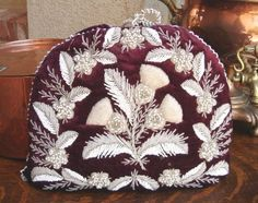 Victorian Velvet & Thread in Feather Design. In America, tea cosies became quite the rage by the late 1800's. Especially in Boston (where they really know how to throw a tea party) when the November 1897 issue of the Boston Journal  provided hints for women on how to construct their own cosy, suggesting the use of embroidered linen or heavy brocade. Currently, in Great Britain, where tea cosies are still popular, most are hand-knitted, resembling wool hats.