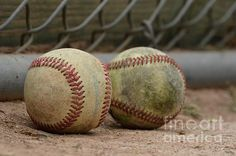 A pair of dirty baseballs lying in the dirt in front of a chainlink fence.  Taken before a baseball tournament at Jack Bulik Park in Fontana, CA.  2016