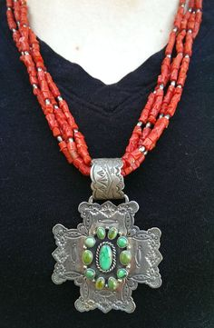 This is a beautiful coral necklace made from 4 ropes of coral and sterling silver beads, with a sterling silver Santa Fe cross pendant. The
