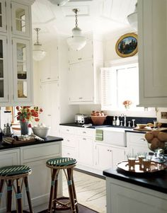 "With its 1930s hanging fixtures from Remains Lighting, this kitchen, designed by Nancy Boszhardt, looks older than it is. A Shaw's Original Apron sink and Rohl faucets add to the effect, as does a ""vintage"" toaster from Williams-Sonoma.   - HouseBeautiful.com"