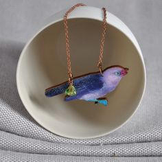 Pretty purple and mauve nuthatch bird necklace from ArtySmartyShop.com, handmade from wood and hung on a copper chain with an intricate Czech glass bead. Whimsical and playful it is perfect as a gift for that bird lover in your life or for yourself!   inspired by the Irish countryside and nature made in our Dublin studio. #artysmartyshop #womensfashion #accessoires #womenswear