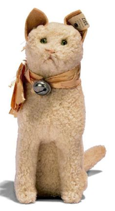 A STEIFF WOOL PLUSH SEATED CAT, (3517), white, green and black glass eyes, felt ears, pink stitching, whiskers, ribbon with bell and FF button with white tag, circa 1907 --6½in. (16.5cm.) high (ribbon perishing)