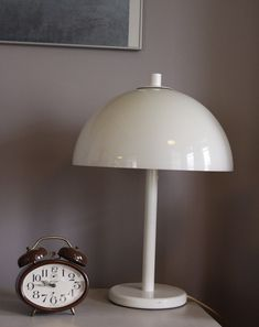 Te koop: geweldige, strak vormgegeven design tafellamp van het populaire merk Dijkstra.     Doet qua vormgeving denken aan de Panthella van Verner Panton en aan de champignon-lampen van Hala.     Komt uit de jaren '60 of '70. Heeft 2 fittingen en een touwtje onder de lamp waarmee je hem aan en uit kunt doet.     Werkt nog perfect! Materiaal: metalen voet, kunststof kap. Originele Dijkstra-sticker zit nog op de lamp.     Prijs: 65 euro