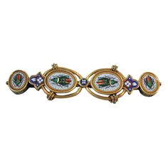 Micromosaic and 18 kt gold bar brooch. Made in Italy, C 1875. Two vertical ovals and 2 horizontal ovals, each with beetle on white ground. Beetles have highlights (foil?). Also, 2 trefoils and 1 circle with polychrome ornament on blue ground. A striking design that incorporates mid-19th-century Gothic motifs. Excellent condition. On silver mount. No missing tesserae.