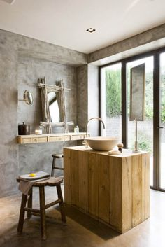 Beautiful unique bathroom with stone walls, branch framed mirror, and island vanity in front of floor length windows.
