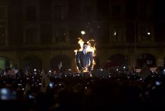 An effigy depicting Mexico's President Enrique Pena Nieto is set on fire during a massive march in Mexico City, Thursday, Nov. 20, 2014. Protesters marched in the capital city to demand authorities find 43 missing college students, seeking to pressure the government.
