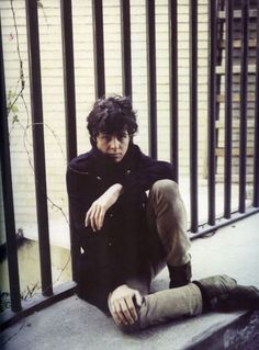 A young Marc Bolan sitting on a ledge looking very mod
