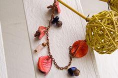 Braccialetto con petali rosa adagiati su una catenina color bronzo...
