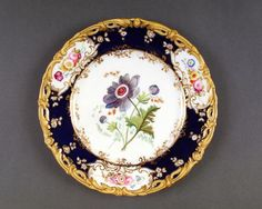 Coalport Porcelain c. 1839-45; the piece is part of a dessert service. Pattern no. 4/412, probably by Stephen Lawrance. The rim is decorated with a broad band of dark blue with three panels of naturally coloured floral groups. The centre is painted with a single flower, Blue Anemone.